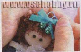 Приклеиваем бантик и бусинки на голову куколки