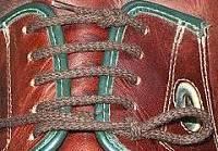 Ботинок со шнурком, завязанным одной рукой